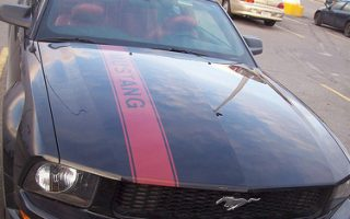 A black Ford Mustang with a red stripe